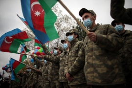 Azeri soldiers hold national flags as they celebrate the transfer of the Lachin region to Azerbaijan's control, as part of a peace deal that required Armenian forces to cede the Azerbaijani territories they held outside Nagorno-Karabakh, in Aghjabadi, Azerbaijan [File Emrah Gurel/AP]