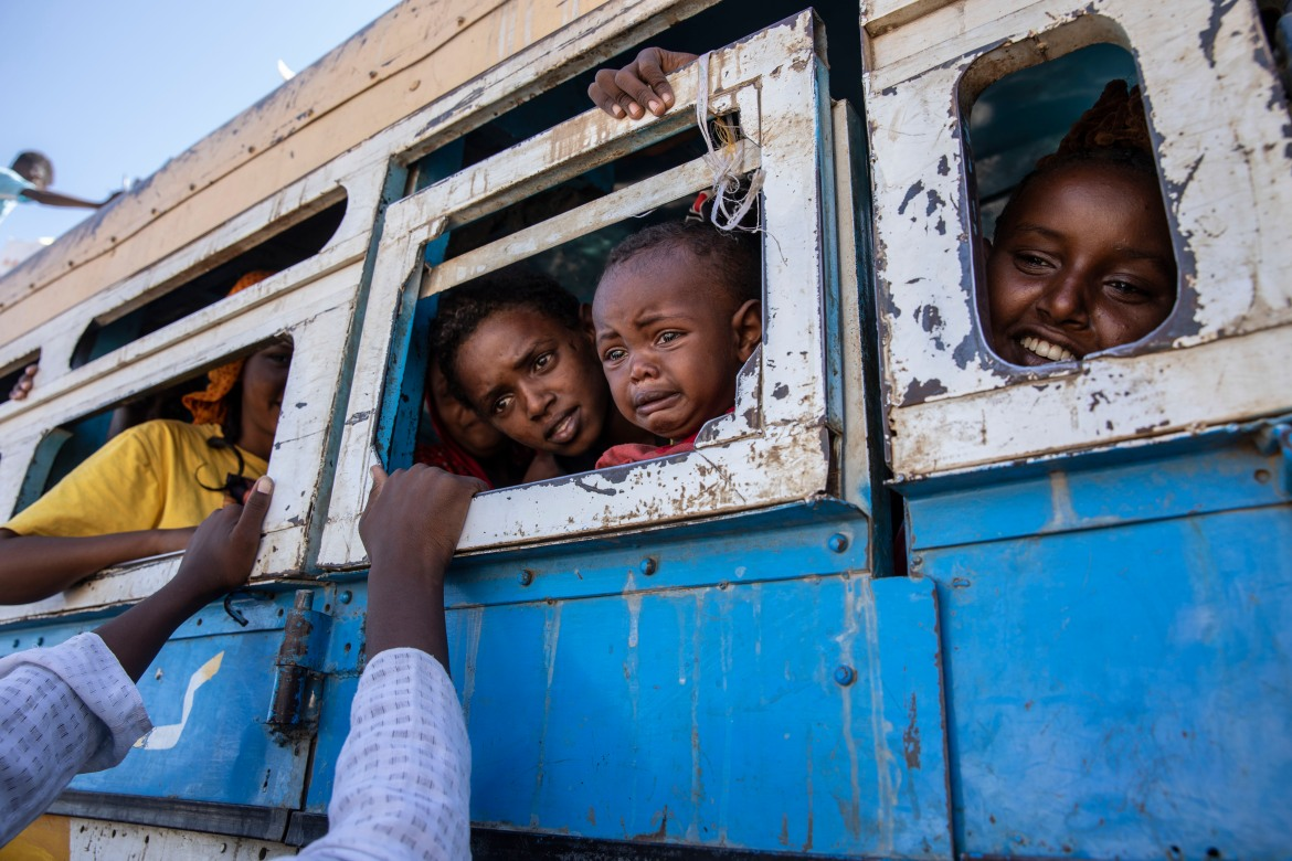 Refugees who fled the conflict in Ethiopia's Tigray region ride a bus headed to the Village 8 temporary shelter near the Sudan-Ethiopia border. [Nariman El-Mofty/AP Photo]
