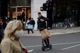 A youngster carries a shopping bag on an electric scooter as non-essential shops are allowed to reopen after England's second lockdown ended at midnight, on Oxford Street, in London, December 2, 2020 [Matt Dunham/AP]