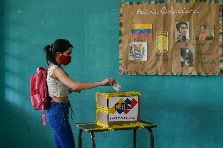 A voter casts her ballot during elections to choose members of the National Assembly in Caracas, Venezuela [Matias Delacroix/AP Photo]