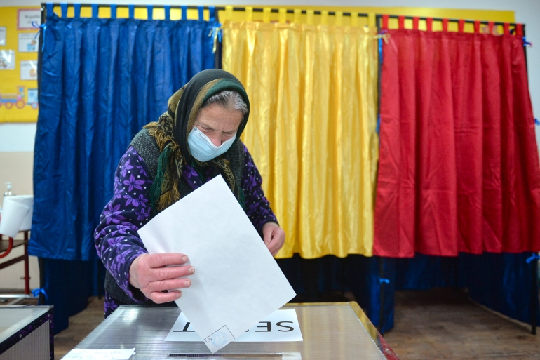 An elderly woman casts her vote in the village of Sabareni, Romania, on Sunday, December 6, 2020 [Alexandru Dobre/AP]