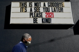 A pedestrian wearing a protective mask walks under a sign in San Francisco, California [Jeff Chiu/The Associated Press]
