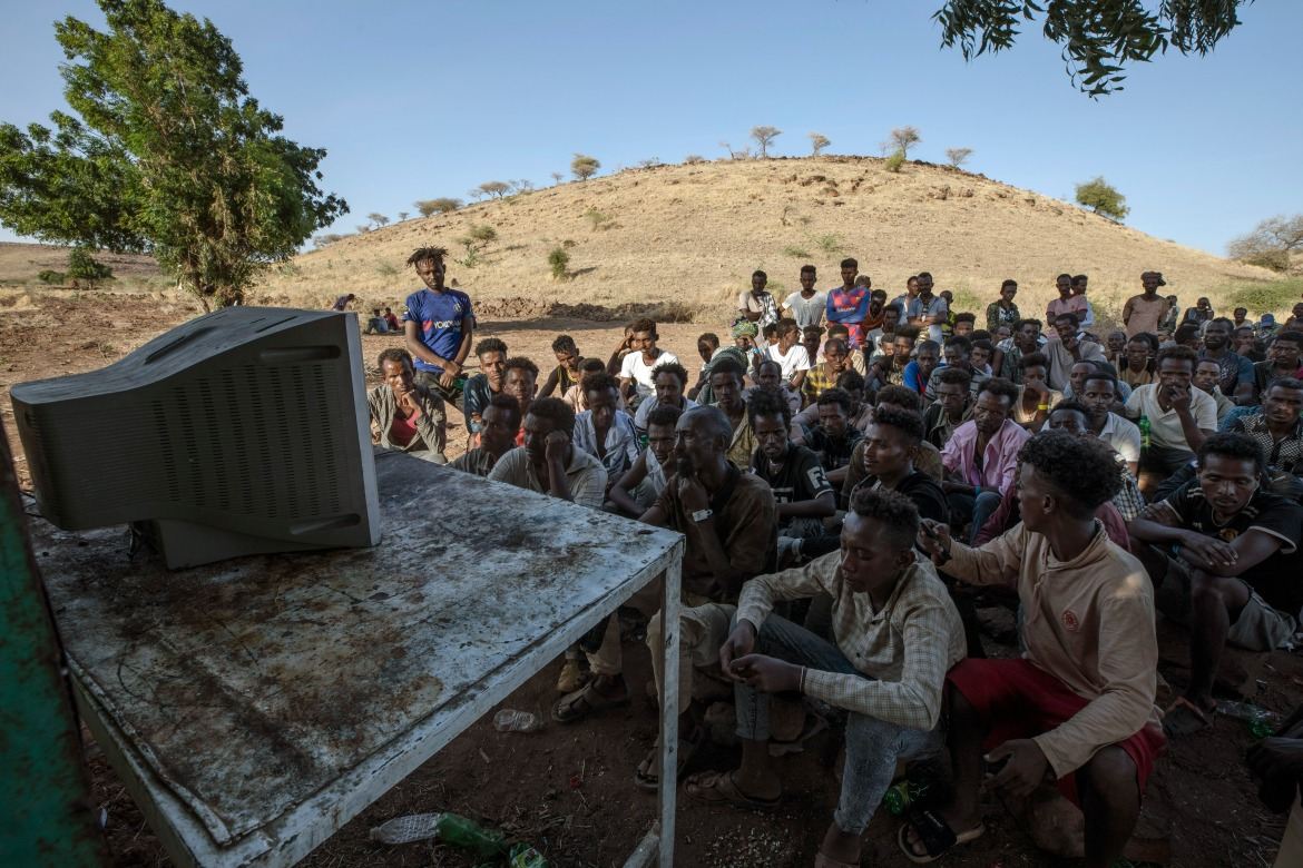 Refugees watch news on television at the Umm Rakouba refugee camp in Qadarif, eastern Sudan. [Nariman El-Mofty/AP Photo]