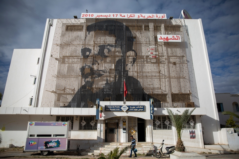 Mohamed Bouazizi is depicted on a post office facade in Sidi Bouzid, Tunisia [Riadh Dridi/AP Photo]