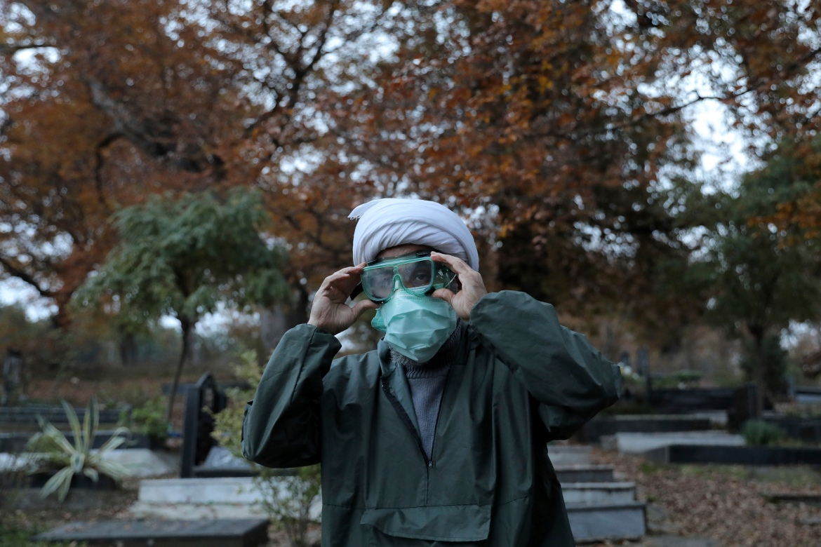 Ali Rahimi, 53, a volunteer Muslim scholar, wears protective clothing at a cemetery in the Arateh village on the outskirts of Ghaemshahr in northern Iran [Ebrahim Noroozi/AP Photo]