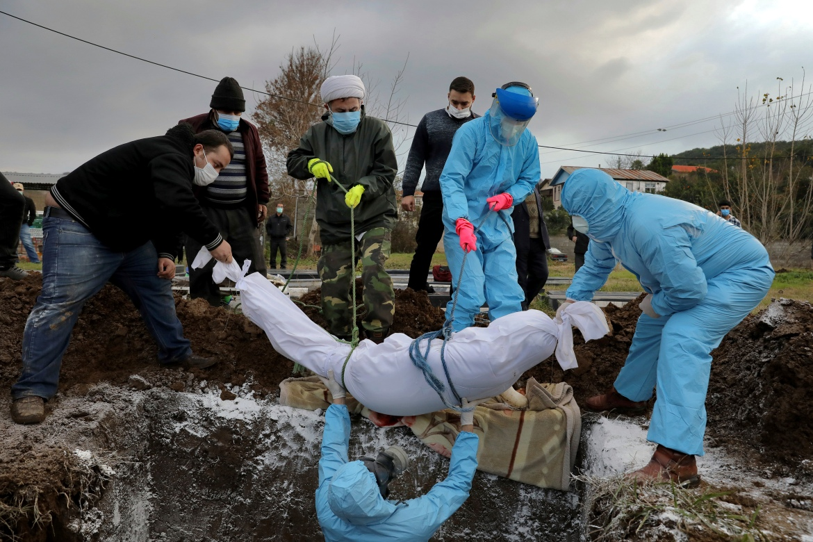 Volunteers and relatives wearing protective clothing and masks lower the body of Ghorbanali Mahmoudi, 59, into a grave at a cemetery in the Haji Kola village on the outskirts of the city of Ghaemshahr. [Ebrahim Noroozi/AP Photo]