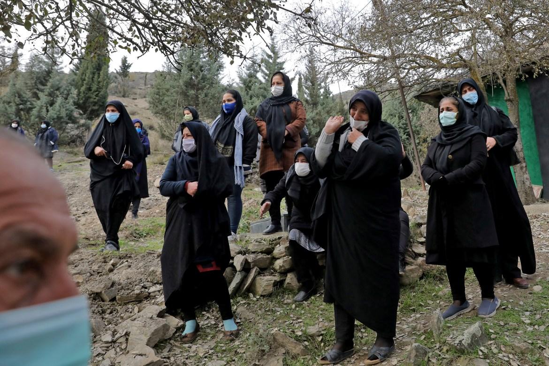 Relatives of Keyumars Ziaee, 60, mourn at a cemetery in the Shir Kola village. [Ebrahim Noroozi/AP Photo]