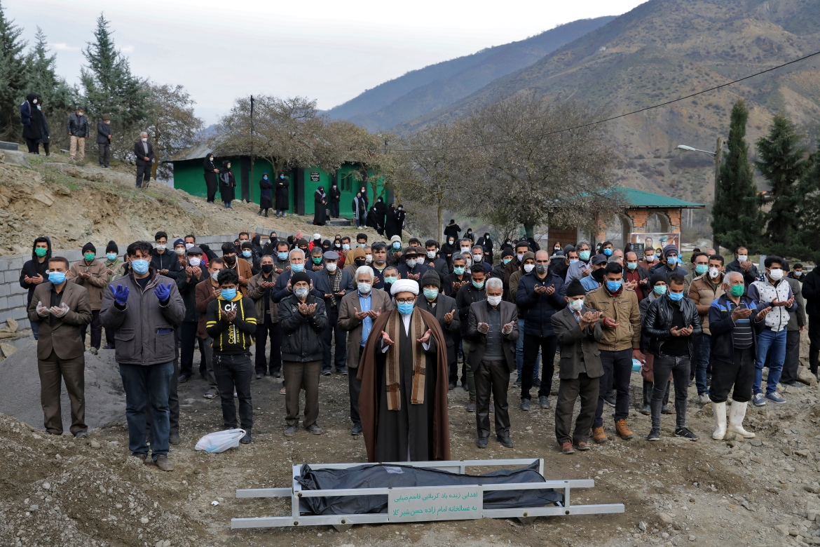 Mourners pray over the body of Keyumars Ziaee, 60, who died from COVID-19, at a cemetery in the Shir Kola village on the outskirts of Ghaemshahr. [Ebrahim Noroozi/AP Photo]