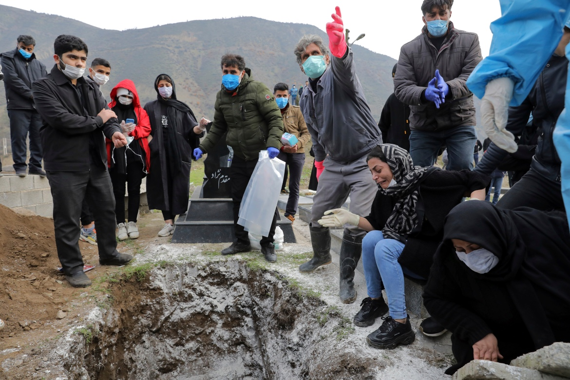 Relatives of Ziaee mourn over his grave at the cemetery. [Ebrahim Noroozi/AP Photo]