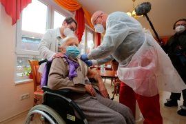 In this file photo from December, nursing home resident Edith Kwoizalla, who is 101 years old, receives a COVID vaccine in Halberstadt, Germany [File: Matthias Bein/DPA via AP Photo]