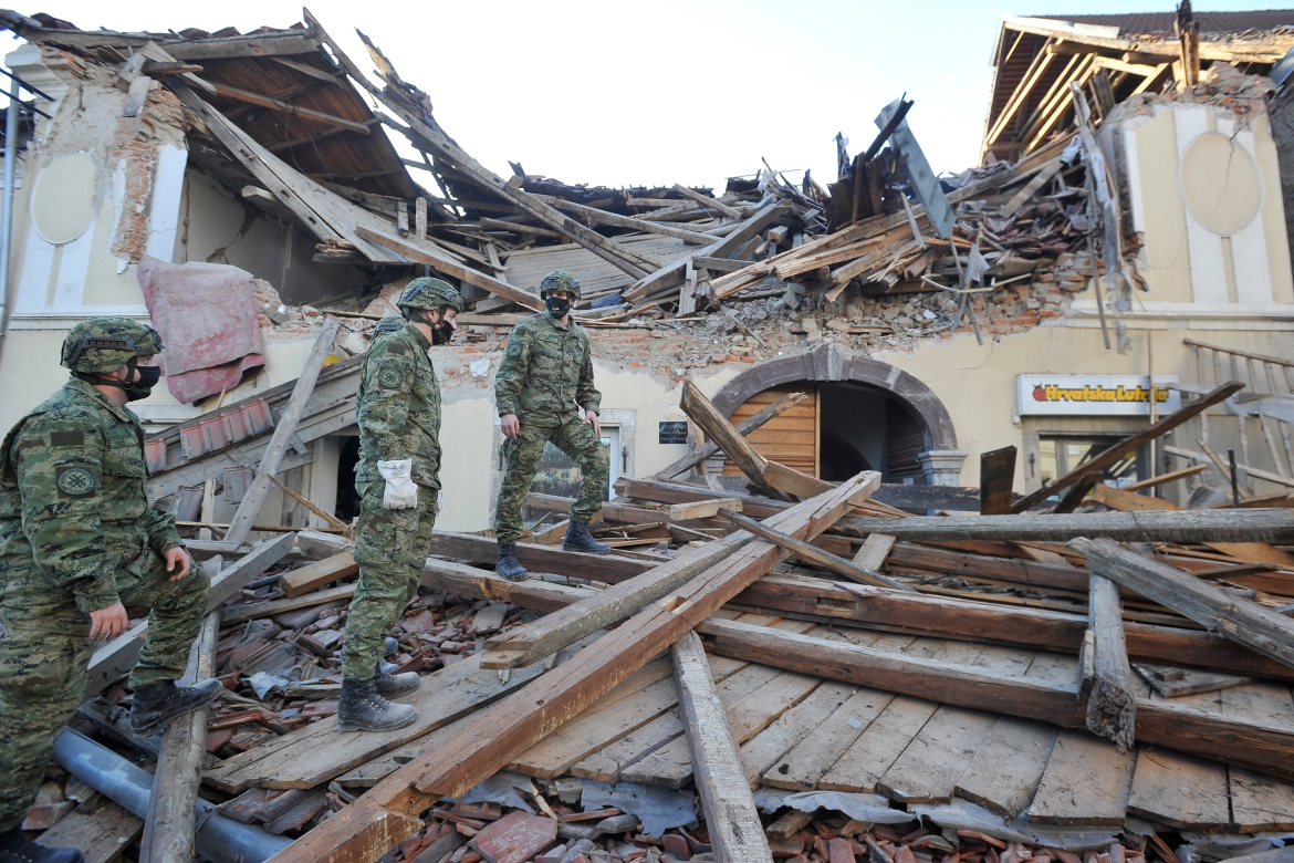 Soldiers inspect the remains of a building damaged in the earthquake, in Petrinja. [AP Photo]