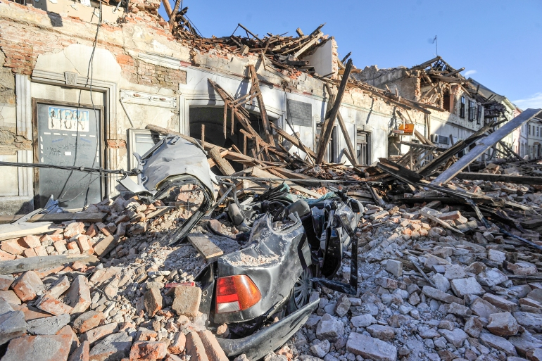 A view of remains of a car covered by debris and buildings damaged in an earthquake in Petrinja, Croatia [AP Photo]