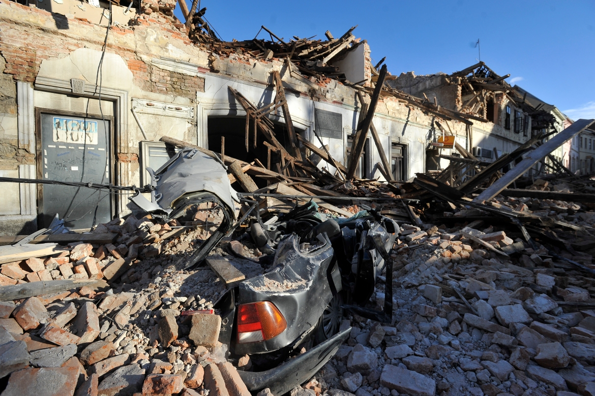 A view of remains of a car covered by debris and buildings damaged in Petrinja [AP Photo]