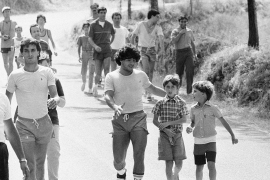 Argentine football icon Diego Armando Maradona talks to a young fan while sightseeing after training with his new team, Napoli in Castel Del Piano, Italy on July 27, 1984 [File: Massimo Sambucetti/AP Photo]