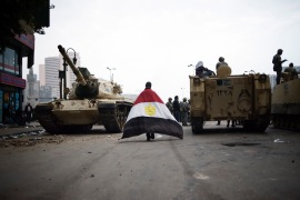 A protester walks between two army trucks as he enters Cairo's Tahrir Square on January 29, 2011 [Alessio Romenzi]