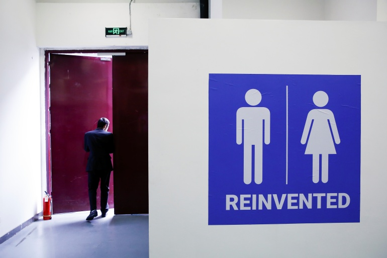 A man walks near a toilet sign at the Reinvented Toilet Expo showcasing sewerless sanitation technology in Beijing, China November 6, 2018. [Thomas Peter/Reuters]