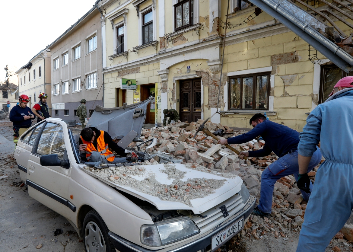 People and soldiers clean up rubble next to a car and buildings damaged in Petrinja. [Antonio Bat/EPA]