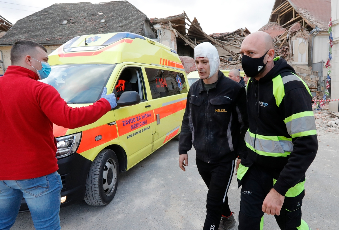 A man with a head injury is escorted away from buildings damaged in the earthquake in Petrinja. [Antonio Bat/EPA]