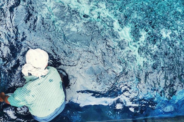 A labourer works in an indigo processing tank where water is oxidised until it turns from greenish to blue [Bala Natrajan/Al Jazeera]