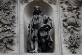 A statue of English merchant and slave trader Sir John Cass is mounted on the wall of the Sir John Cass Foundation in central London [File: Tolga Akmen/AFP]