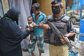 A policeman stands guard as a health worker marks the finger of a child after administering polio vaccine drops in Karachi [File: Rizwan Tabassum/AFP]