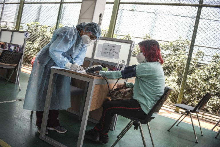 A volunteer has a medical checkup inside the clinical studies centre of the Cayetano Heredia University before being vaccinated with the Chinese potential vaccine against COVID-19 in Lima in December [File: Ernesto Benavides/AFP]