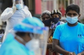 Residents wait in a line to get tested for the coronavirus in Colombo [File: Ishara S Kodikara/AFP]