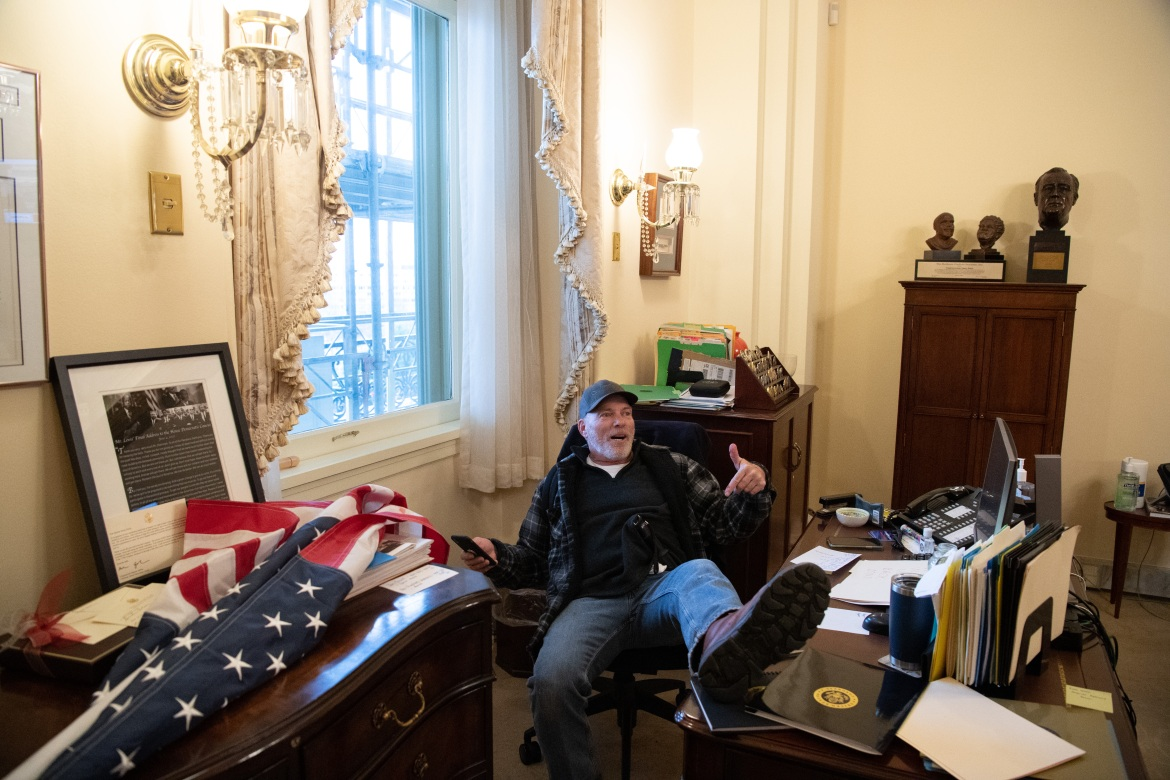 A supporter of US President Donald Trump sits inside the office of US Speaker of the House Nancy Pelosi as he protest inside the US Capitol in Washington. [SAUL LOEB / AFP] (AFP)