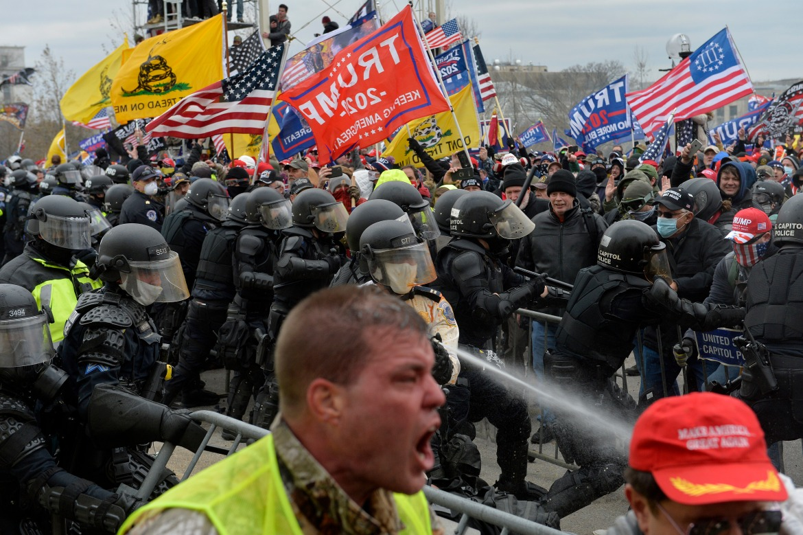 Trump supporters clash with police and security forces as people try to storm the Capital Building in Washington. [Joseph Prezioso/AFP]