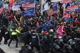 Trump supporters clash with police and security forces as they push barricades to storm the US Capitol in Washington, DC on January 6, 2021 [Roberto Schmidt/AFP]