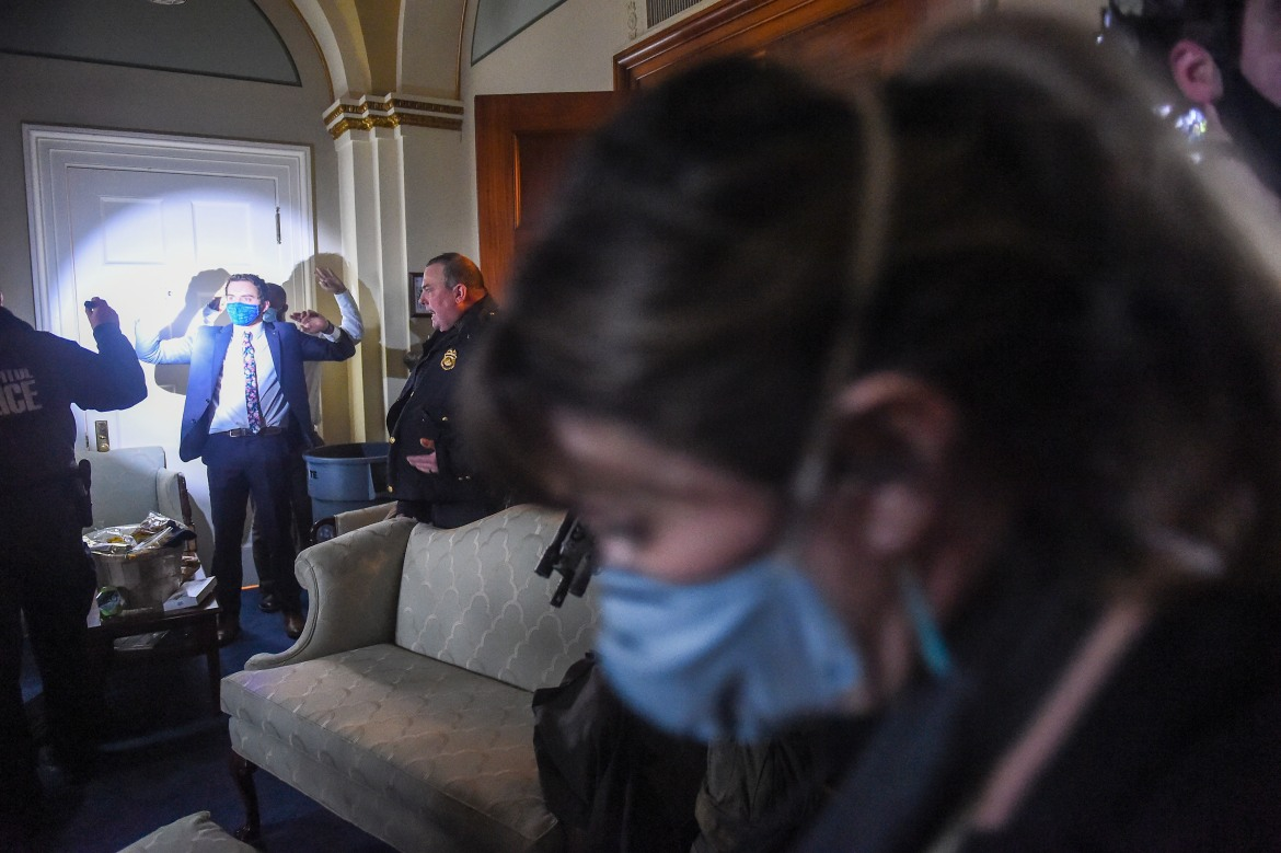 A Congress staffer holds his hands up while a Capitol Police SWAT team checks everyone in the room searching for Trump supporters who breached the building. [Olivier Douliery/AFP]