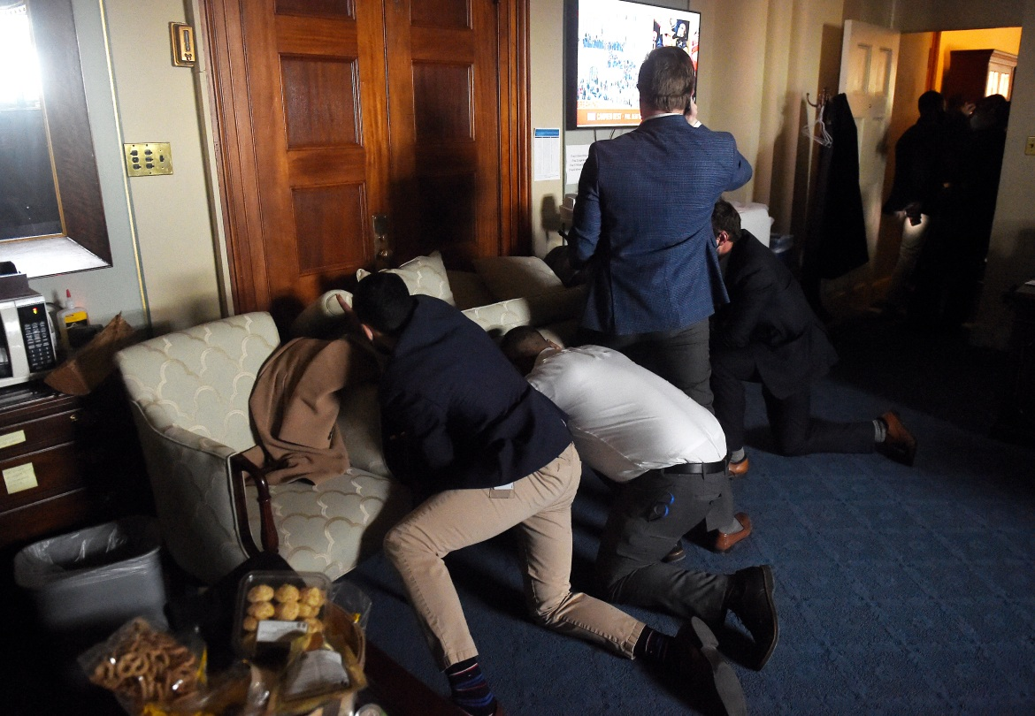 Congress staffers barricade themselves inside offices after Trump supporters stormed the US Capitol. [Olivier Douliery/AFP]