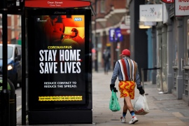 A shopper walks past NHS signage promoting 'Stay Home, Save Lives' on a bus shelter in Chinatown, central London, UK [Tolga Akmen /AFP]