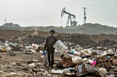 A child sifts through a rubbish dump near an oil field in the countryside of al-Malikiya in northeast Syria. [Delil Souleiman/AFP]