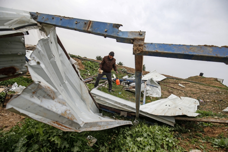 A Palestinian man salvages items at the scene of an Israeli attack near the Palestinian city of Khan Younis in the southern Gaza Strip [File: Said Khatib/AFP]