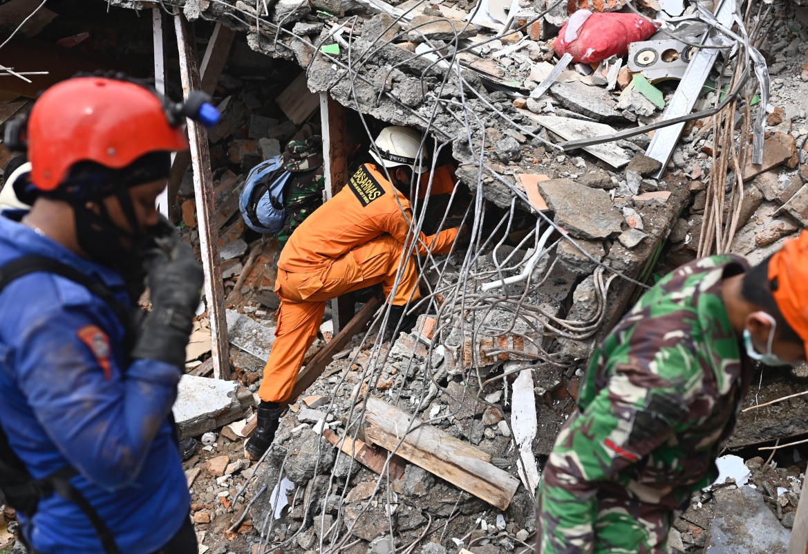 Tim penyelamat mencari korban di reruntuhan bangunan yang runtuh di kota Mamuju.  [Hariandi Hafid / AFP]