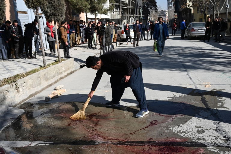 A resident washes a road after gunmen killed two female judges working for the Supreme Court in the capital [Wakil Kohsar/AFP]