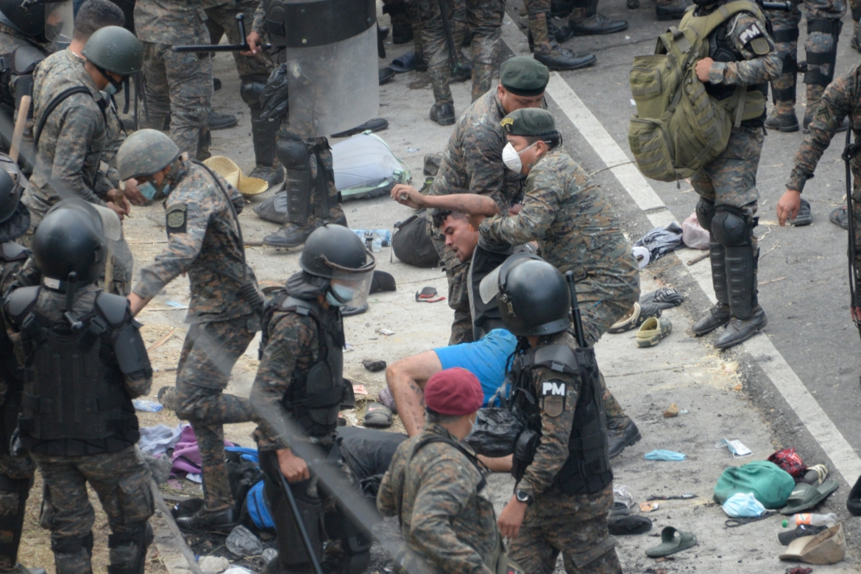 Guatemalan soldiers detain a Honduran migrant. [Johan Ordonez/AFP]