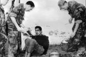 In this file photo taken on March 14, 1957 French paratroopers question Algerian Omar Merouane in Saint Eugene [Jacques Grevin/Intercontinentale/AFP]