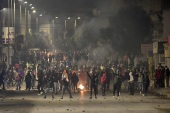 Clashes also broke out in poor areas of Tunis, including el-Tadamen and Sijoumi, as hundreds of angry youths burned tyres and blocked roads [Fethi Belaid/AFP]