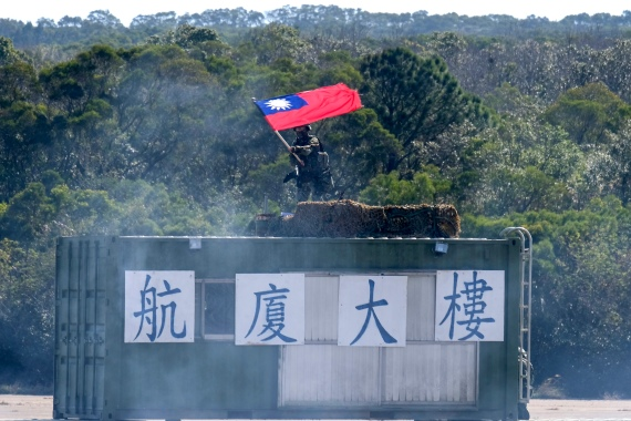 A Taiwanese soldier waves a Taiwan national flag during a military exercise in Hsinchu County, northern Taiwan, on January 19, 2021 [Sam Yeh/AFP]