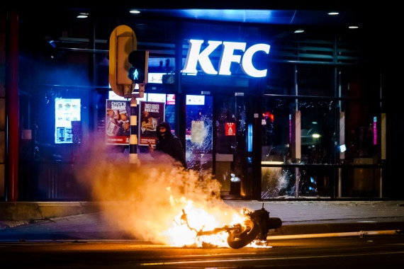 A vehicle is set on fire by demonstrators outside a restaurant in Rotterdam. [Marco de Swart/ANP/AFP]