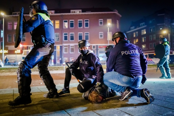 Dutch policemen arrest a man in Rotterdam during a third night of unrest over a nationwide COVID-linked curfew [Marco de Swart/ ANP via AFP]