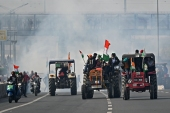 Farmers hold tractor rally as they ride through the smoke of tear gas fired by the police in New Delhi [Sajjad Hussain/AFP]