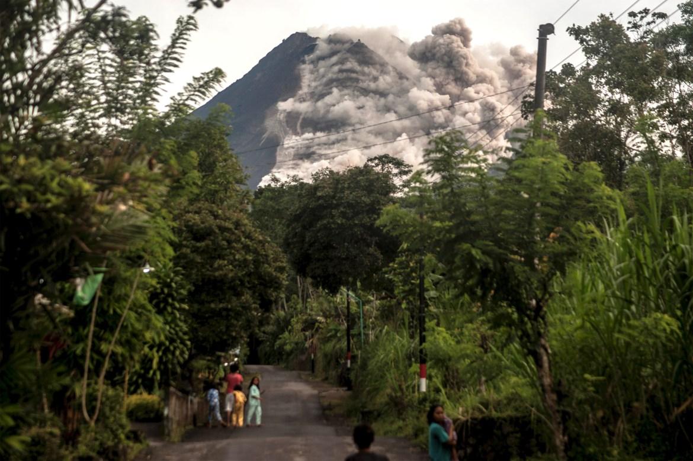 Orang-orang memandang Gunung Merapi, gunung berapi paling aktif di Indonesia, karena menyemburkan batu dan abu.  [Agung Supriyanto / AFP]