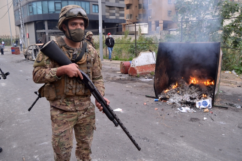 A Lebanese soldiers stands next to a burning dumpster during ongoing demonstrations in Tripoli [Fathi Al-Masri/AFP]
