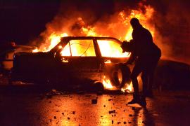 Lebanese protesters burn a vehicle in the northern port city of Tripoli. [Fathi al-Masri/AFP]