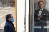 A man in Moscow, Russia, wearing a protective mask, walks past advertisements for the movie No Time to Die, the latest installment in the James Bond series, whose global theatre release has been postponed until October [File: Tatiana Gomozova/Reuters]