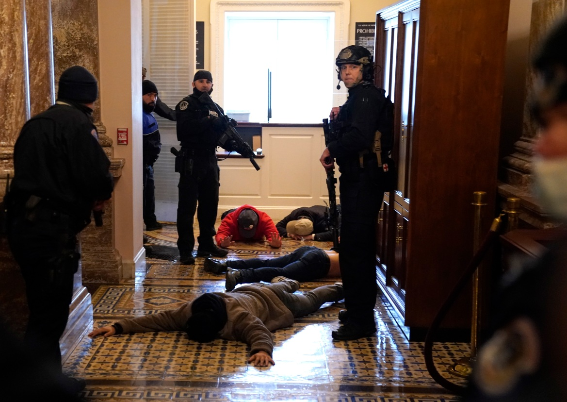 US Capitol Police stand detain protesters outside of the House Chamber during a joint session of Congress. [Drew Angerer/Getty Images/AFP]