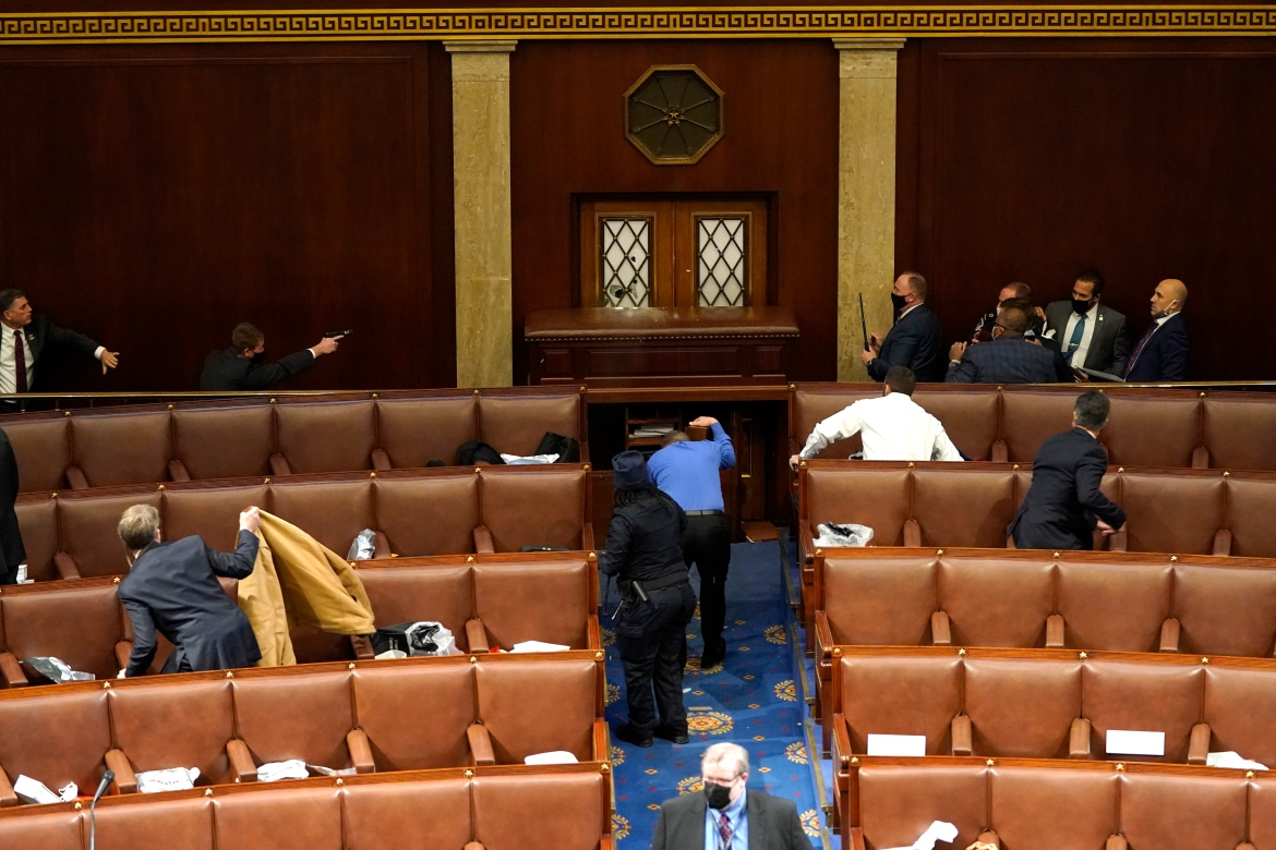 US Capitol police officers point their guns at a door that was vandalized in the House Chamber during a joint session of Congress. [Drew Angerer/Getty Images/AFP]